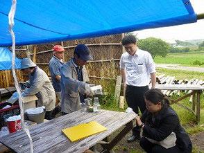 興正寺の二人(右)にロウソクの再利用を説明