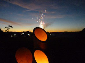 夏祭りで打ち上げられた花火とと竹灯篭