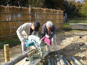 竹を裁断する大木さん、木村会長(右)