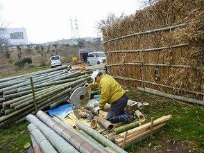 電動丸のこで竹を裁断する山田さんです