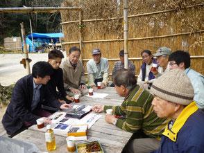 東京から来訪された鶴川さん(左)の説明を聞く会員