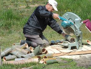 3本組灯篭の竹を切る山田さん