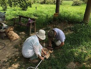 草刈機の手入れをする若松さんと新美さん(左)