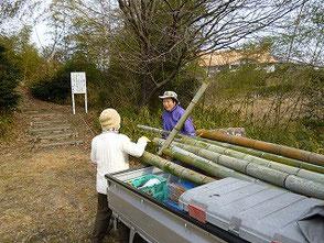 竹を軽トラックに積み込む越間さん(左)、吉田(幹)さん
