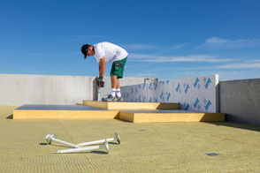 Un ouvrier fixe des plaques d'isolants sur la toiture d'un IME