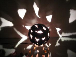 Fetzenkugel Objekt illuminiert oder im neutralem engobierten Ton.  Lichtreflektion hervorgehoben durch Öffnungen von Fetzenübergängen in der Kugel.