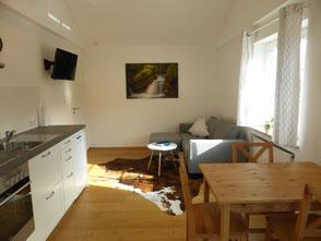 Durch einen separaten Eingang gelangen Sie in den offenen Wohn-/Essbereich mit sichtbaren Deckenbalken, naturbelassenen Holzmöbeln und einem Eichendielenboden
