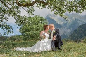 Brautpaar sitzt romantisch unter einer Eiche