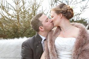 Küssendes Brautpaar im Winter auf einer Bank mit Fell