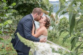 Brautpaar küsst sich zwischen Blättern am See