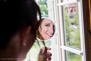 Braut schaut in den Spiegel beim Getting Ready