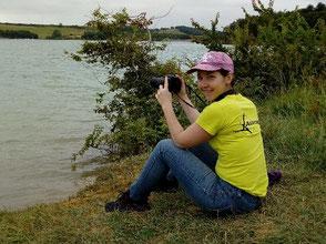 Hélène Maréchal,  avec un appareil photo, au bord de l'eau avec un tee-shirt jaune fluo du windfoil Aeromod
