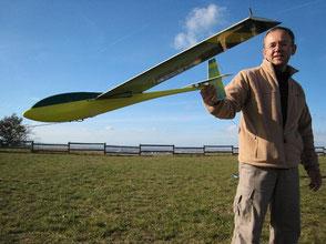 un homme tient un planeur coquillaj Aeromod par la queue, pour un lancement à la catapulte