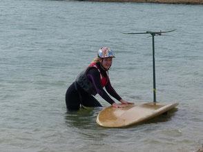 Célia Maréchal,  en combinaison et casque, dans l'eau avec une planche à voile et un windfoil Aeromod