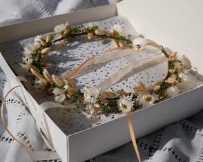 Couronne de fleurs naturelles pour la mariée. Teintes blanc ivoire, vert et dorée.