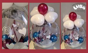 transparenter Latexballon in weiss, beere und blau gestaltet und mit Gutschein und Glückwunschkarte gefüllt