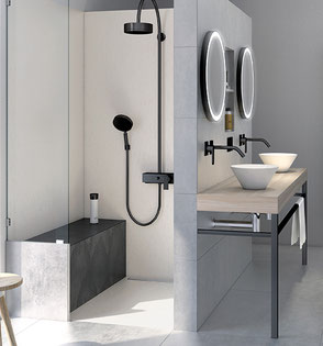 Modern-style bathroom with white tiled curbless shower with a line drain, a black tiled bench, and black shower head. There's a vanity with two white vessel sinks, round mirrors,  and black faucets on a gray tiled wall.