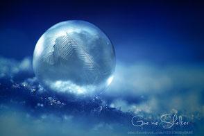 Kühles Wintermotiv in Aquamarinblau, gefrorene Seifenblase mit Blatmuster auf Schnee