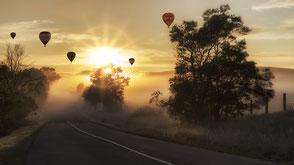 Heißluftballongs über einer Landstraße, bei Nebel und Sonnenaufgang