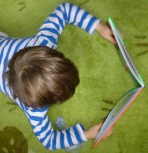 Kind mit einem Buch vor sich