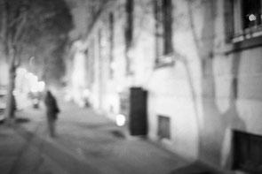 jeromedevismes. Une silhouette la nuite dans une rue de Brest avec beaucoup d'ombres d'arbres sur les murs