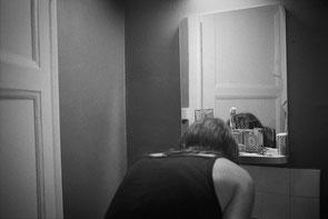 jeromedevismes. dans une chambre d'hôtel une femme de dos en débardeur