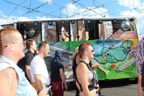 """""""Zug der Liebe"""" in Berlin 25.7.2015, Menschen neben bunt bemaltem Wagen. Foto: Helga Karl"""
