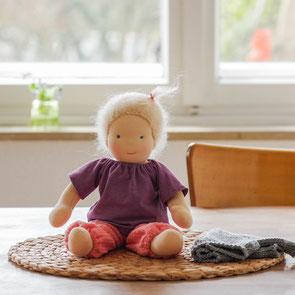 Kleine Puppe wie Waldorfpuppe 30 cm groß mit blonden Haaren aus Mohair Wolle mit lila Pulli und pinker Musselin Hose sitzend