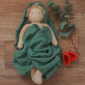 Wunschpuppe Individuelle Puppe nach Waldorfart zur Bestellung liegt eingehüllt in grünen Musselinstoff auf einem Holztisch