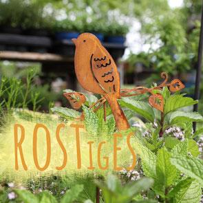 """Gartenstecker in Form eines Vogels in Rostoptik in eine Minze-Pflanze gesteckt. Bild hat eine orangene Aufschrift """"Rostiges""""."""