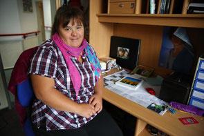 Eine junge Dame sitzt an ihrem Schreibtisch und blickt lächelnd in die Kamera.