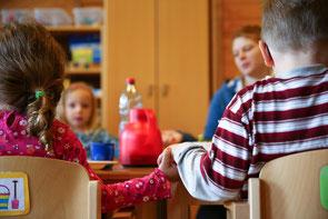 Vier Kinder bei der Vorlesestunde.