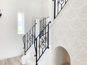 階段〜二階吹き抜け迄のスチール手すり、ロートアイアン調の唐草をふんだんに使ったアイアン手摺