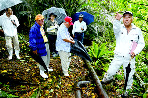 施設跡を視察した参加者。松島委員(右)が送水管を前にして解説した=9日、市内宮良