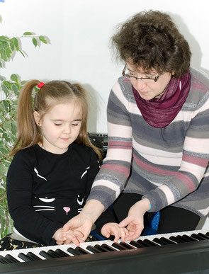 Foto: Frau Pevzner legt jungen Schülerin die Finger auf die Tasten