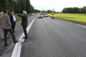 Markus Schwizer, Leiter der Uzwiler Bauverwaltung, mit einer Handvoll Interessierter auf der Baustelle Radweg/Niederstetterstrasse. Im Bild eine von mehreren Ausweichstellen für Lastwagen, bei denen die sonst nur 5 m breite Fahrbahn 6,30 m breit ist. Hint