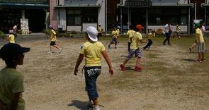 校庭で鬼ごっこをする子供たち