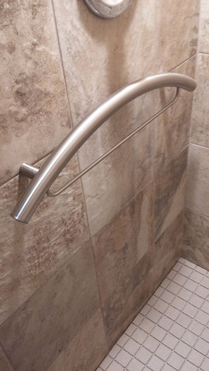 Close up of brushed nickel curved TileWare grab bar with a integrated towel bar. The grab bar is in a shower with rough, slate-like ceramic tiles on the wall and white square 2-by-2 inch tiles on the floor.
