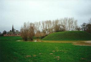 Vue de la motte d'Ochtezeele avec ses fossés en eau à l'occasion d'une crue de la Peene Becque (en arrière-plan, l'église qui fut probablement construite à l'emplacement de la première chapelle seigneuriale)