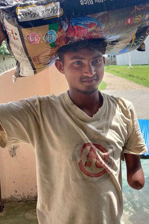 Mann mit amputierem Unterarm und Reissack auf dem Kopf