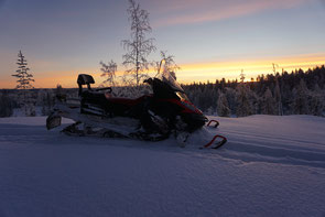 Schneemobil im Sonnenaufgang