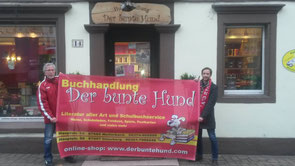 """Das Foto zeigt Hans-Werner Fuhrmann (Vorstand Verwaltung FVW) und Uwe Neu (Inhaber """"Der bunte Hund""""), die gemeinsam vor dem Geschäft in der Hauptstraße das Banner präsentieren."""