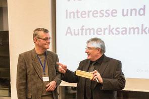 """Friedemann Preu, Sprecher Forum Betriebliche Konfliktkultur, überreicht Dr. Martin Wolmerath (rechts) ein """"Streitschlichter-Stückchen"""""""