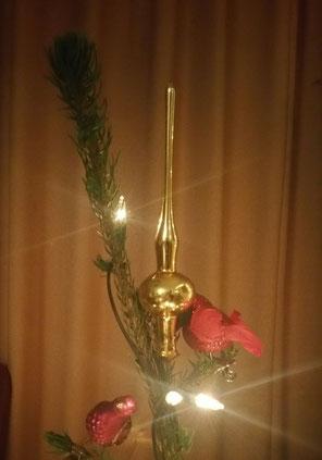 bovenste stuk van een kerstboom. De boom groeit naar boven toe scheef weg, en op een klein zijtakje prijkt een kleine gouden piek. Twee rode vogeltes versieren het geheel, en drie lichtjes stralen feestelijk.