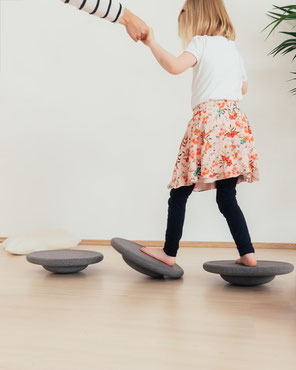 Kind balanciert auf Stapelstein BALANCE BOARD grey basic