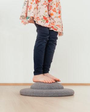 Kind balanciert auf einem Stapelstein BALANCE BOARD grey
