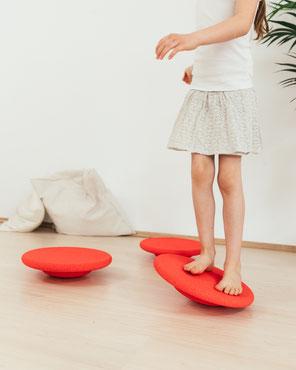 Kind balanciert auf Stapelstein BALANCE BOARD red basic