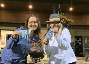 """Photo of Friday Night Lights winners Jen Newman and Pat Rawluk holding $5 bills and a """"trophy""""."""
