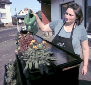 Anne Katharina Schmitt gießt ein schwarzes Klavier, das zu einem Blumenbeet umgebaut worden ist.