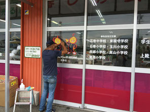 ガラスへカッティング文字を貼っていきます/豊橋の石巻の衣料品店